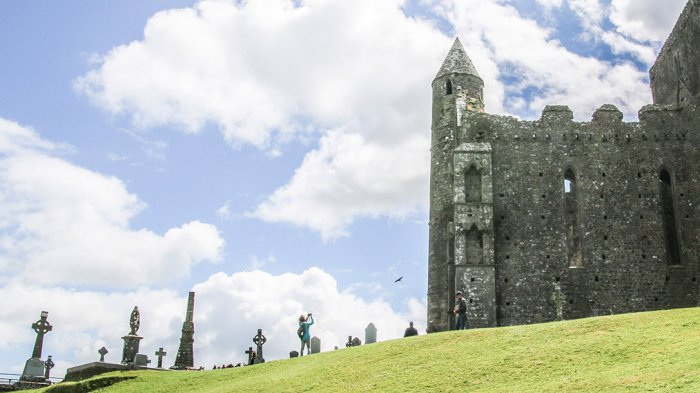 Celtic crosses in graveyard with tall tower and church at Rock of Cashel