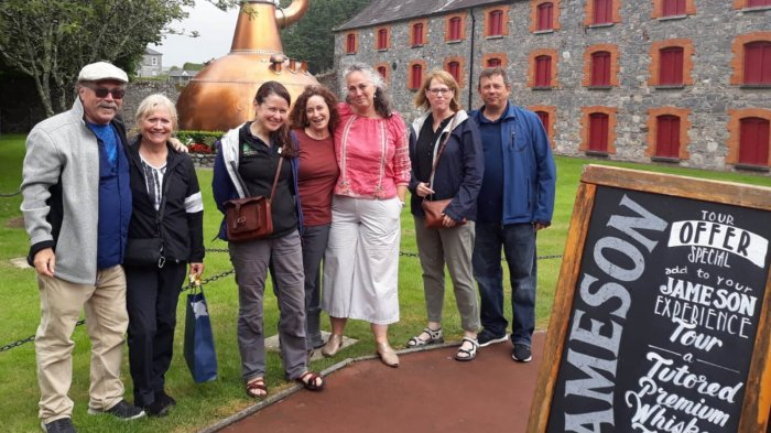 A smiling Driftwood tour group on a guided tour of the Jameson Whiskey Distillery in Midleton, Ireland