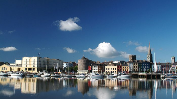 Quays in Waterford city showing buildings and reflection in river