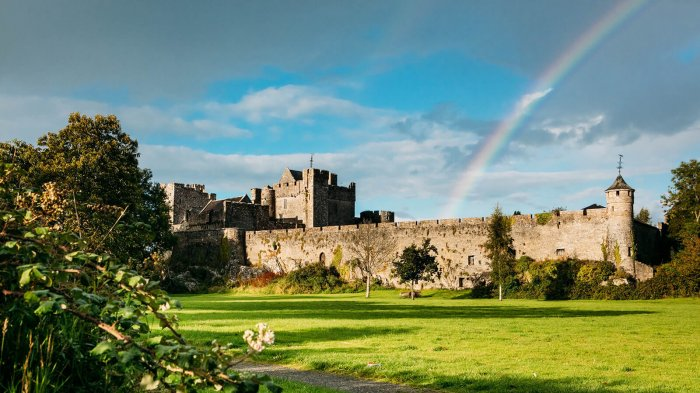 A rainbow over Cahir Castle walls with sunlit foliage in the foreground