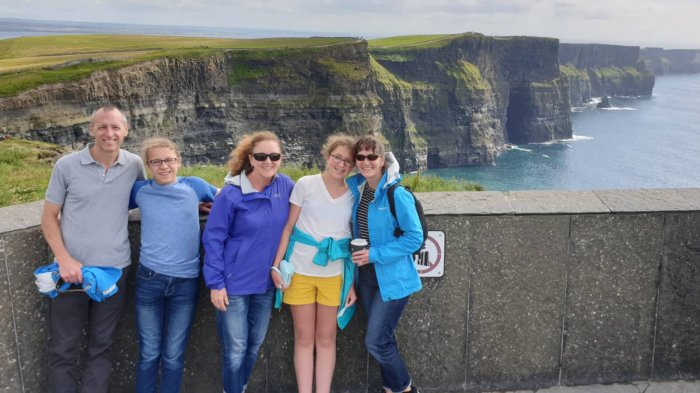 Smiling family tour group at the Cliffs of Moher, Ireland