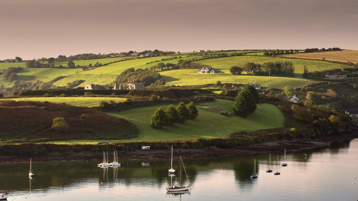 Kinsale harbour in Ireland with green fields in the background and boats on tranquil water in the foreground