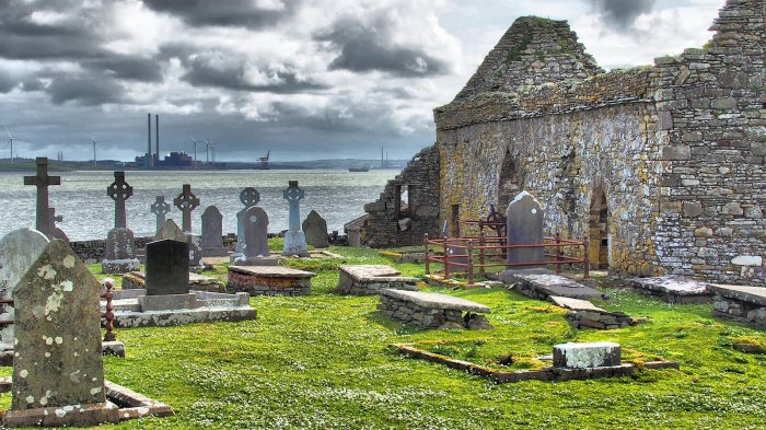 Graveyard and ruined church on Scattery Island in Ireland with dark clouds overhead and factory chimneys on the horizon over a stretch of water