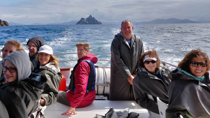 Smiling tour group on board a boat trip to the Skellig Islands, Ireland