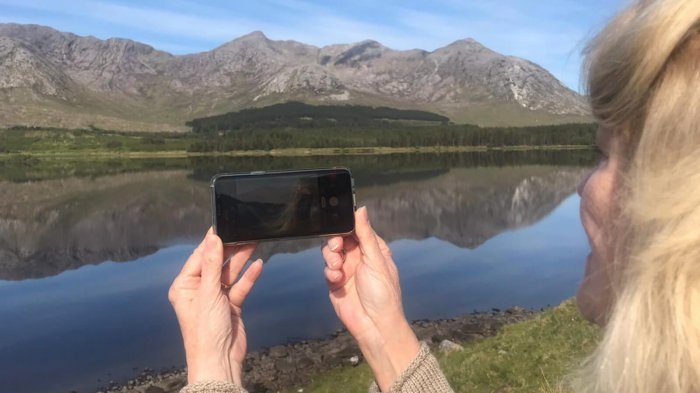 Tour guest holding a phone in front of a scenic lake and mountains landscape in Connemara, Ireland