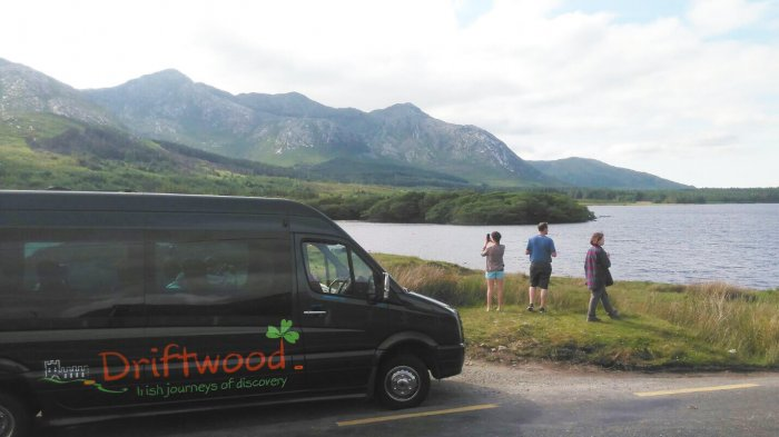 Drifter tour vehicle with guests looking at a stunning Connemara landscape