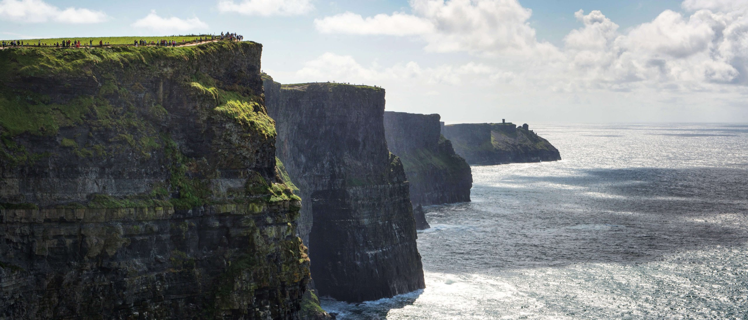 Dramatic shot of very small people standing on top of the Cliffs of Moher in Ireland