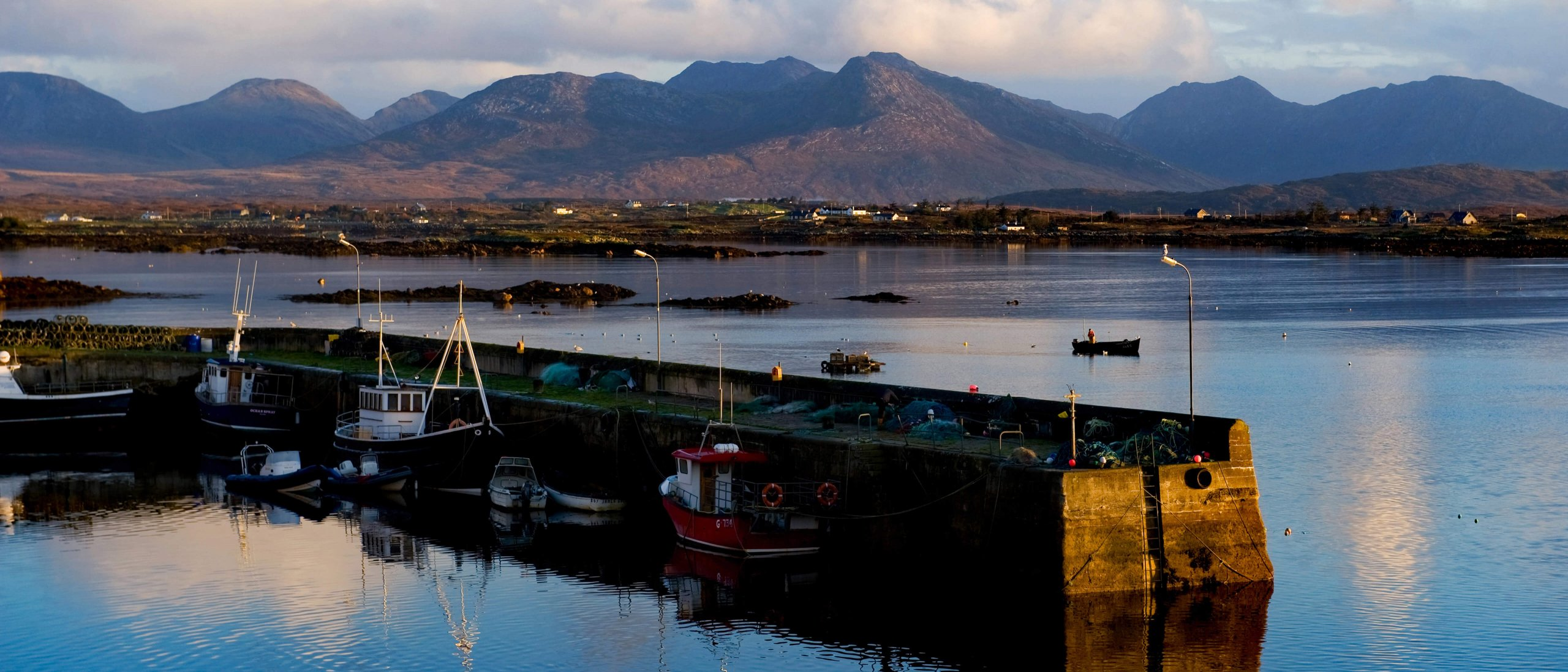 Pier in Roundstone with Connemara mountain range in background