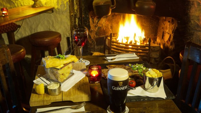 A pint of Guinness stout/beer with a selection of Irish foods in front of a roaring fire in Ireland