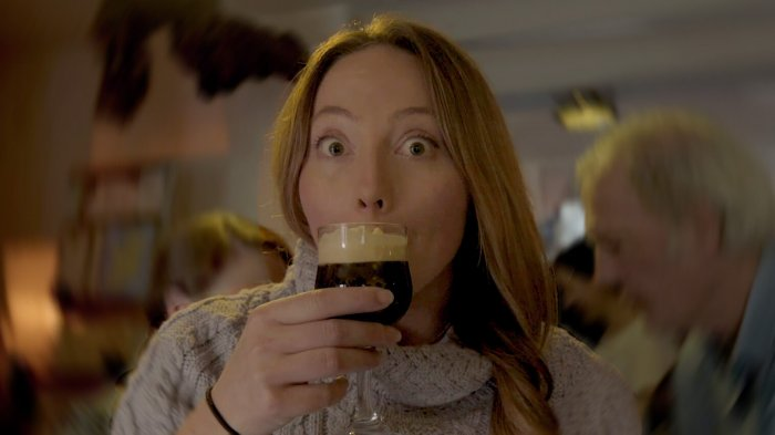 Female tour guest raises her eyebrows and widens her eyes at the camera while sipping from an Irish coffee