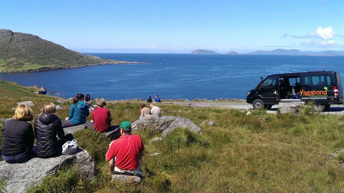 A Vagabond group relaxing with a picnic in a scenic coastal location with a VagaTron tour vehicle stopped nearby