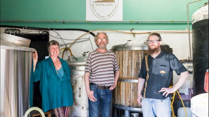 Three brewers stand facing the camera in West Kerry Brewery, Ireland