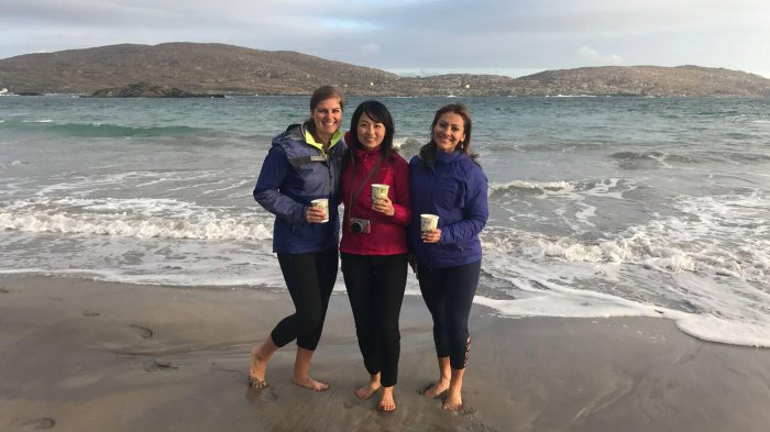 Three female Vagabond guests stand together in the waves on a beach in Ireland, holding coffee cups