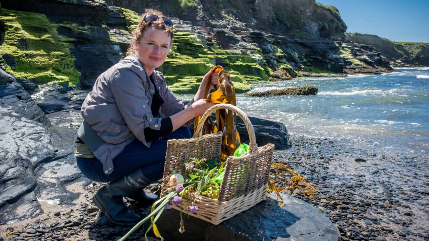 Oonagh Dwyer poses at a coastal location with a selection of foraged food including seaweed