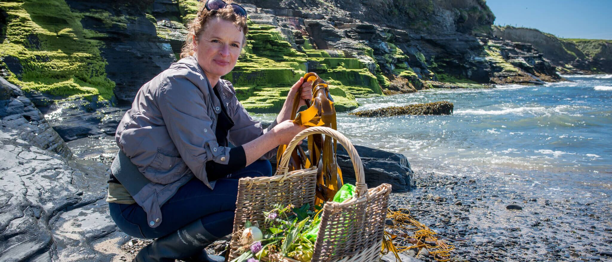 Oonagh Dwyer of Wild Kitchen posing at the coast with a basket of foraged seaweed