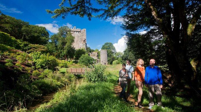 Two men and Two women walking through the Blarney Gardens with Blarney Castle in the background