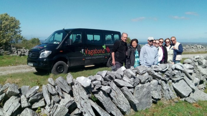 Vagabond tour group behind a dry stone wall with a VagaTron tour vehicle behind