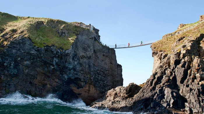 Three distant figures cross Carrick a rede rope bridge in Northern Ireland