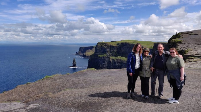 A family of four posing at the Cliffs of Moher in the sunshine