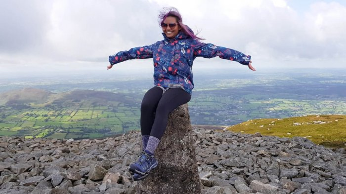 Female tour guest sitting on top of the summit of Slieve Gullion mountain summit in Ireland