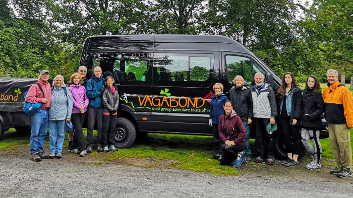 A group of Vagabond guests posing in Killarney National Park in front of a Vagabond vehicle