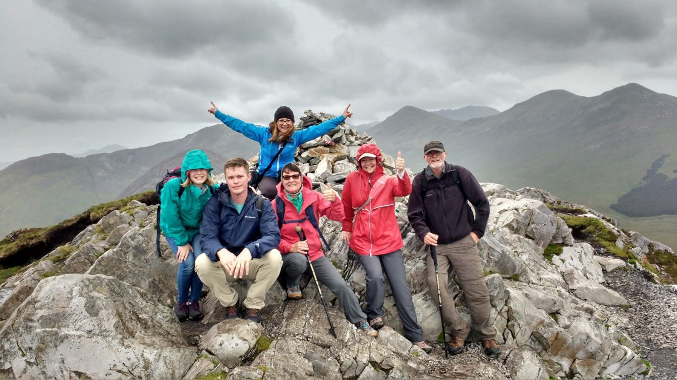 Vagabond tour group smiling at the summit of Diamond Hill in Connemara, Ireland