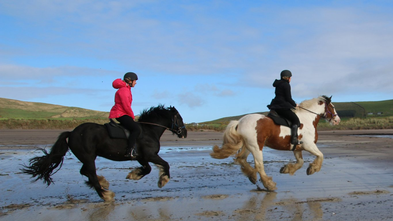 Two horse riders galloping along a beach