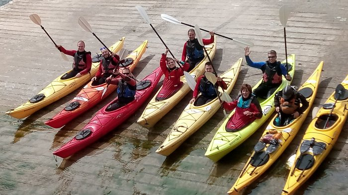 Group of Vagabond guests waving their paddles while sitting in kayaks on a slipway