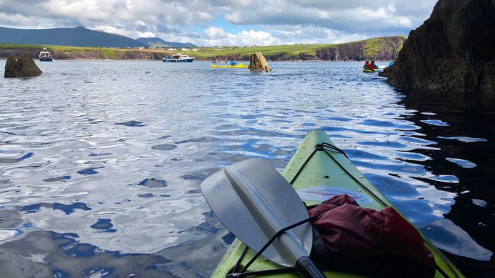 A view of Dingle Bay taken from a kayaker with a view of the top of the kayak in the bottom left corner