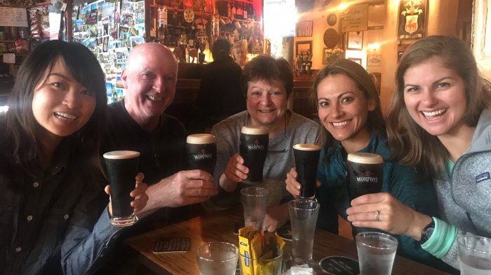 Five happy Vagabond tour guests toast the camera with pints of stout in a pub in Ireland - cheers!