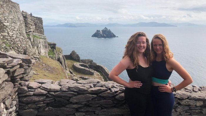 Two female Vagabond tour guests at the summit of Skellig Michael in Ireland with Little Skellig island in the background