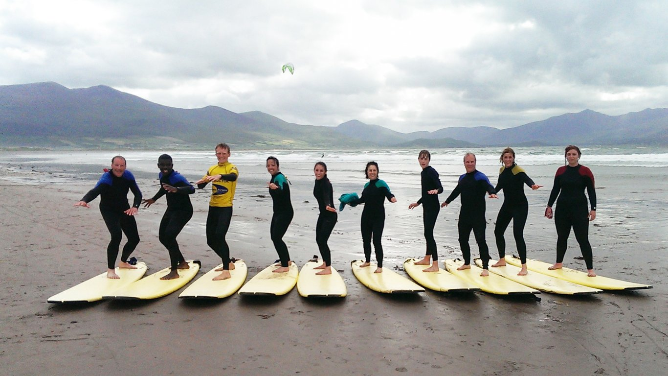 A Vagabond tour group standing on surfboards in Kerry, Ireland