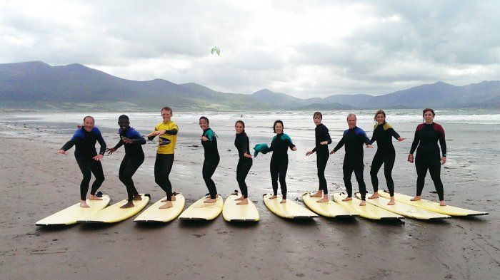 Surfing group on Castlegregory beach with mountains in the background