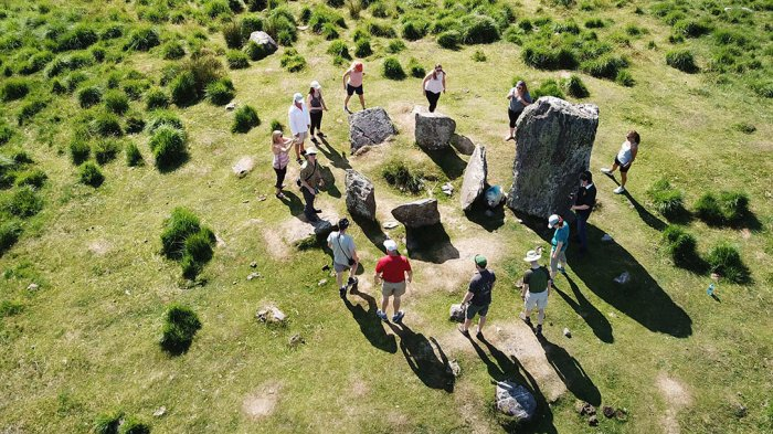 A group of Vagabond guests dancing around in a circle around the Uragh Stone Circle