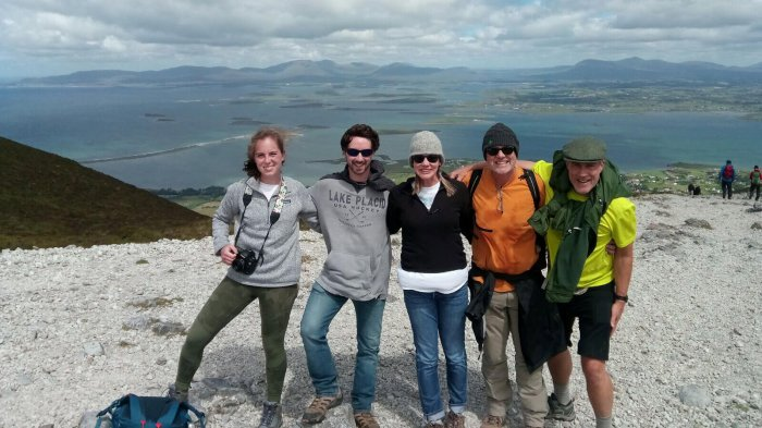 Vagabond group hiking Croagh Patrick in Ireland with a scenic view of Clew Bay in the background