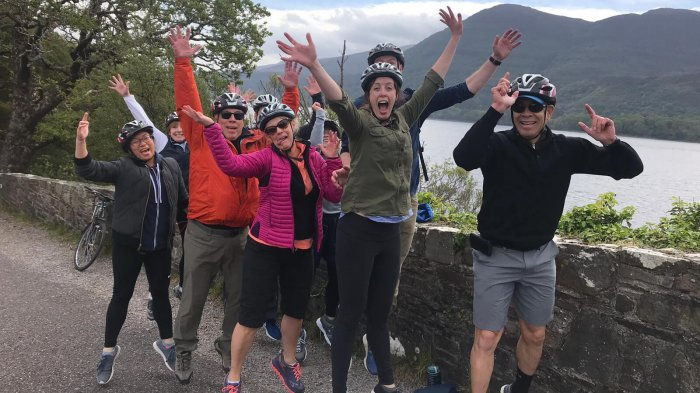 Happy Vagabond tour guests wearing cycling helmets and jumping in Ireland