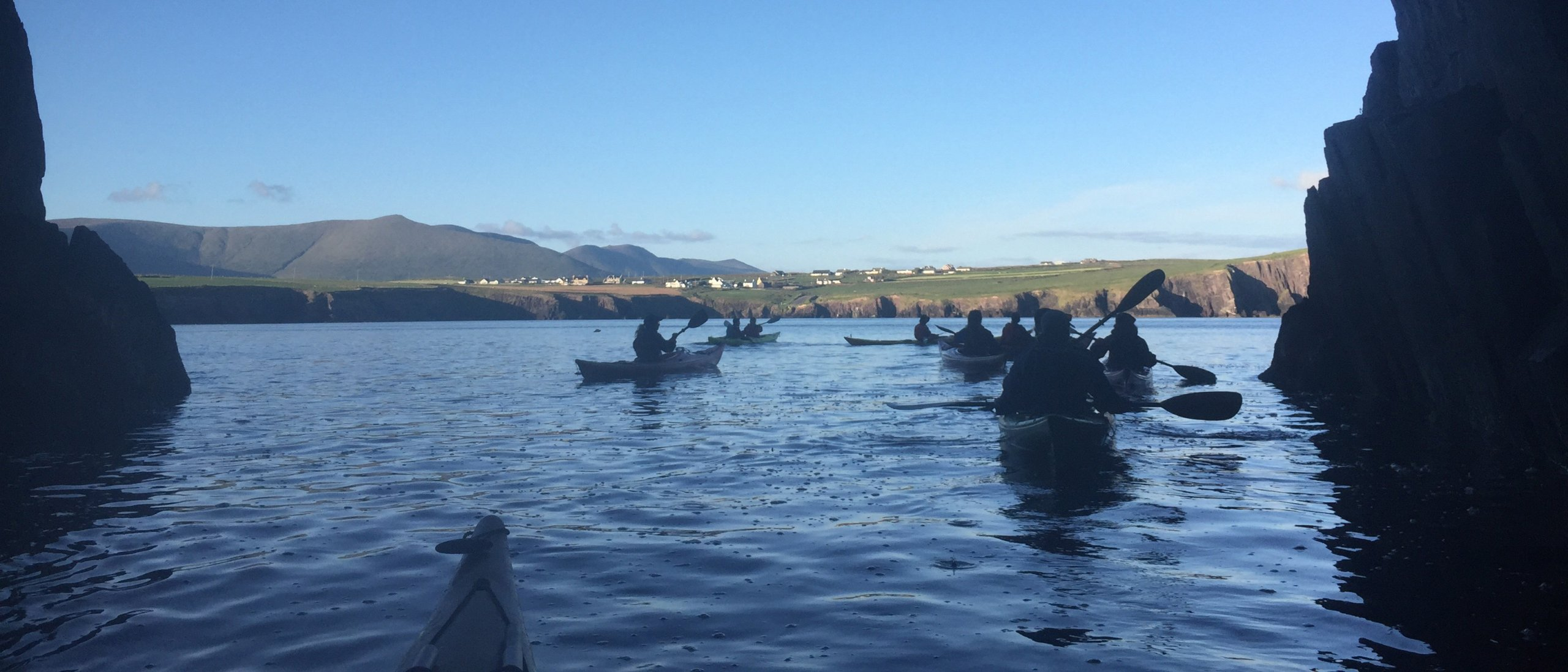 A group of kayakers paddling out of a sea cave in Dingle Bay, Ireland