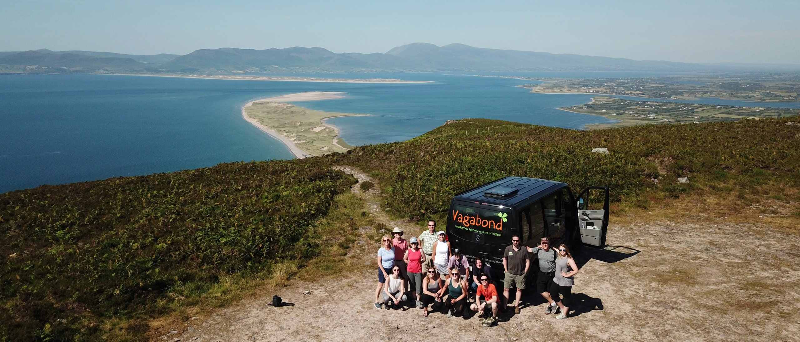 Vagabond VagaTron Tour Vehicle and group posing at Rossbeigh in Kerry