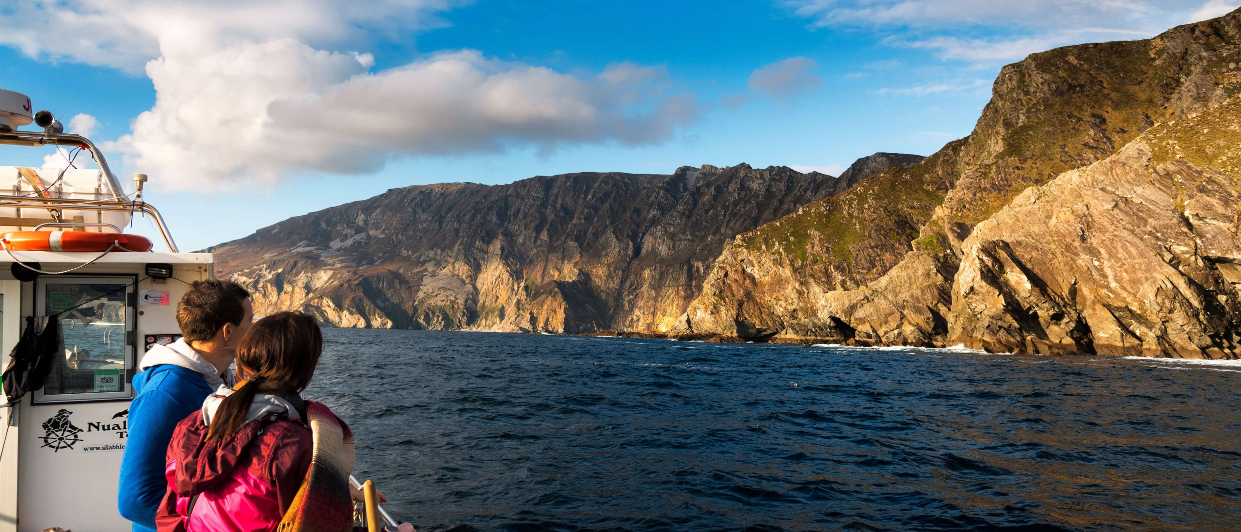 A man and a woman on a boat trip underneath the Slieve League cliffs in the sunshine