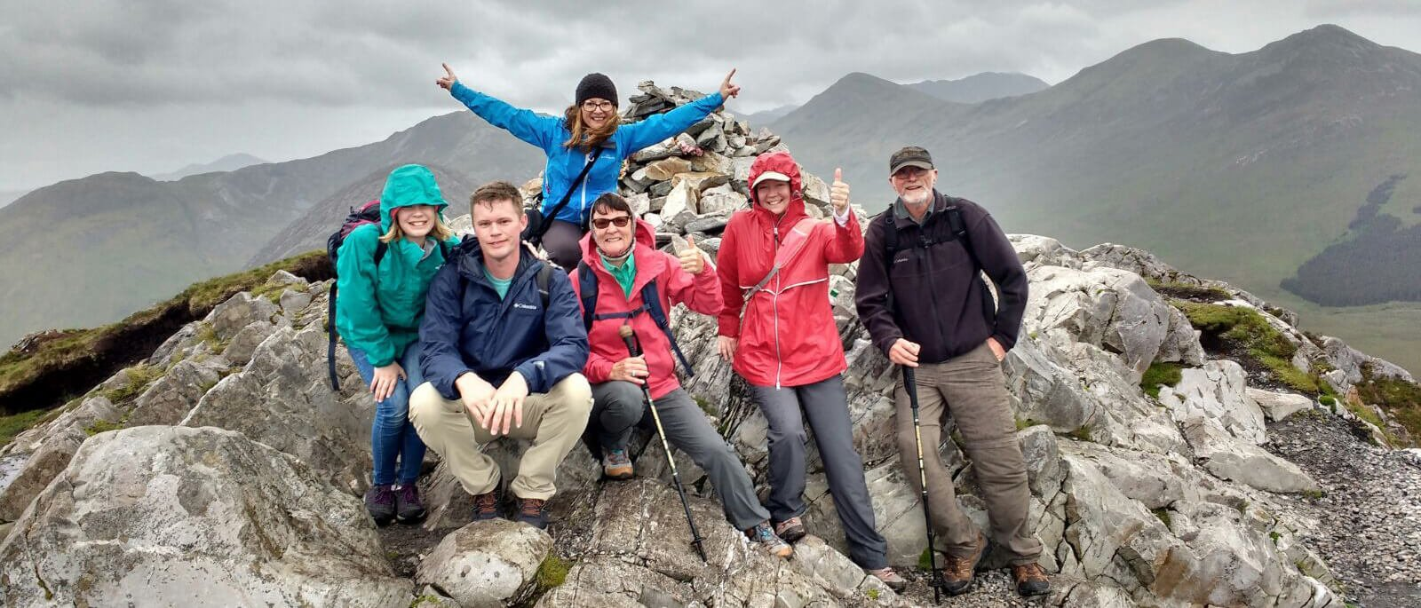 Group of Vagabond tour guests looking satisfied at the summit of Diamond Hill in Connemara