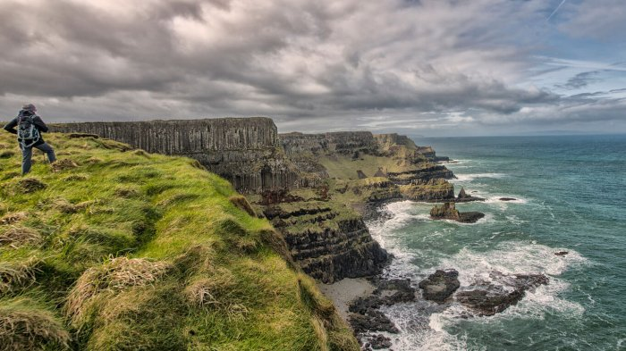A lone hiker looks out over a scenic coastal scene of cliffs, moody clouds and big waves