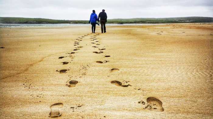 A couple walking on Maghera beach in Donegal holding hands leaving footprints behind them