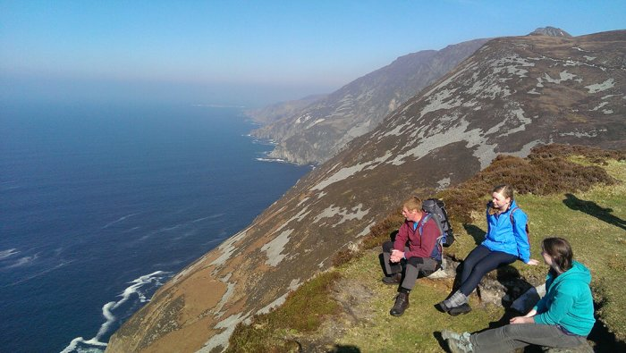 Three people sitting on top of a mountain overlooking Slieve league