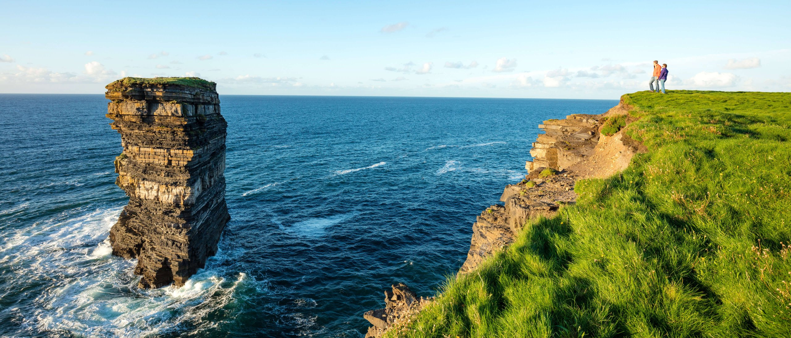 Couple look at Downpatrick Head sea stack from headland in Mayo