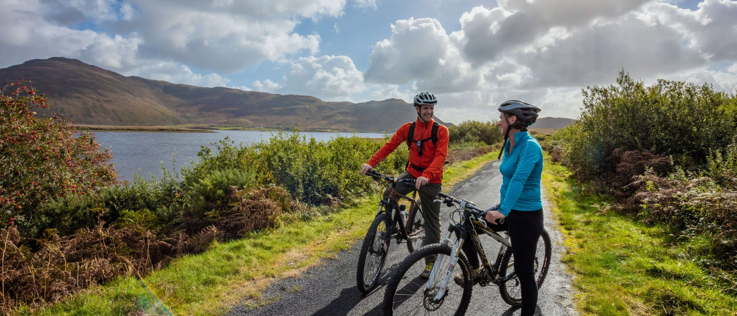 Couple cycling stop with their bikes at scenic spot on Great Western Greenway in Mayo