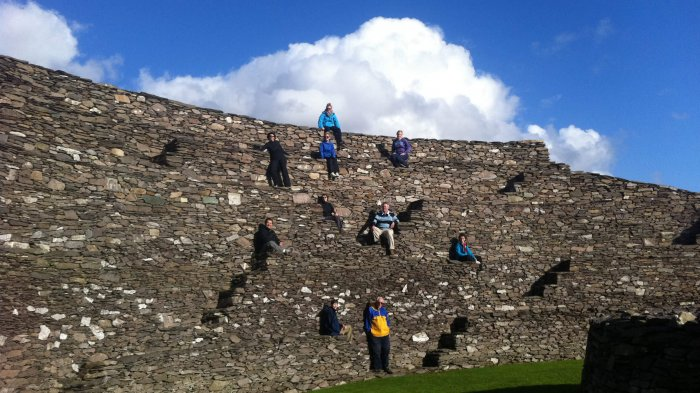 Vagabond Tours group standing at different levels of a stone wall on the interior of Grianán of Aileach fort in Donegal