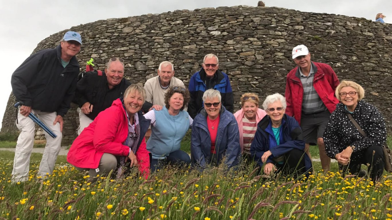 Smiling middle aged tour group at Grianan of Aileach in Ireland