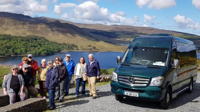 A smiling Driftwood tour group pose beside their Drifter tour vehicle at a scenic location in Ireland