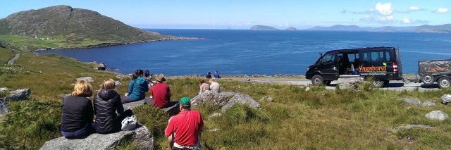 A Vagabond Tour Group picnicking in a scenic location in Ireland with a 4x4 VagaTron tour vehicle parked nearby