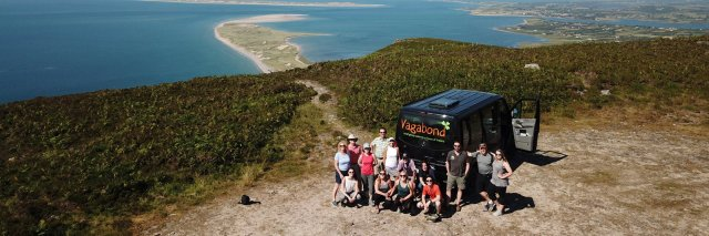 Vagabond Tour Group posing beside VagaTron 4x4 tour vehicle at a scenic mountain site in Ireland